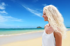 Blondevrouw met lang krullend blond haar op strand Stock Fotografie
