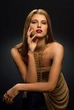 """Blondevrouw met omhoog gestileerd make†"""", lange halsband en vele ringen op haar vingers Stock Foto"""