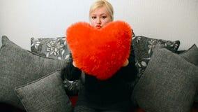 Blondevrouw met rood gevormd hoofdkussenhart stock footage