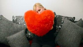 Blondevrouw met rood gevormd hoofdkussenhart Heilige Valentine en Internationale Vrouwen` s Dag, Acht 8 Maart stock videobeelden