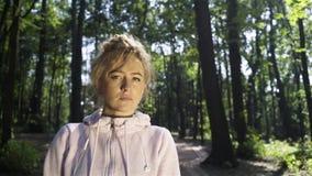 Blondevrouw met sproeten in een bos die en aan u draaien glimlachen stock video