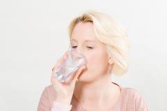Blondevrouw over Wit Drinkwater Als achtergrond van Plastic C royalty-vrije stock fotografie