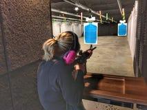 Blondevrouw schieten AR-15 Stock Foto