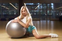 Blondevrouw in sporten die het stellen met zilveren yogabal kleden Royalty-vrije Stock Foto