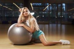 Blondevrouw in sporten die het stellen met zilveren yogabal kleden Stock Foto's