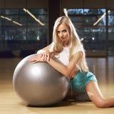 Blondevrouw in sporten die het stellen met zilveren yogabal kleden Stock Fotografie