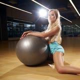 Blondevrouw in sporten die het stellen met zilveren yogabal kleden Stock Afbeeldingen
