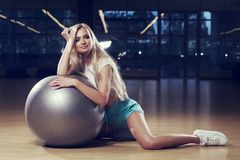 Blondevrouw in sporten die het stellen met zilveren yogabal kleden Stock Foto