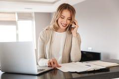 Blondevrouw stellen die thuis binnen gebruikend laptop computer die door mobiele telefoon spreken zitten stock foto's