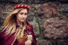Blondevrouw stellen die zich met zwaard in rode kleren bevinden stock foto