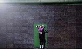 Blondewijfje die op springen, tegen de modieuze achtergrond van de groendeur, openlucht Royalty-vrije Stock Afbeeldingen