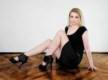Blondezitting op de vloer Stock Foto's