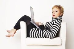 Blondgirl agradável que senta-se na cadeira com portátil Fotografia de Stock