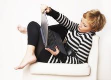 Blondgirl agradável que senta-se na cadeira com portátil Imagem de Stock