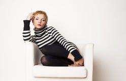 Blondgirl agradable en la silla Fotografía de archivo libre de regalías