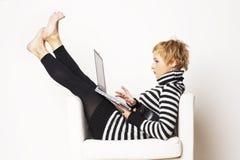 Blondgirl agradable que se sienta en la silla con la computadora portátil Imágenes de archivo libres de regalías