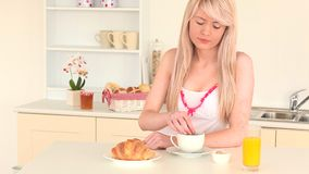 Blondhaired woman having her breakfast Royalty Free Stock Photography