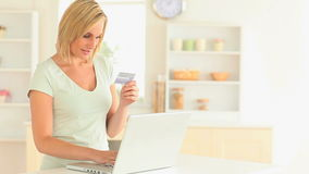 Blondhaired woman paying online stock video footage
