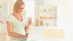 Blondhairedvrouw die online betalen stock videobeelden