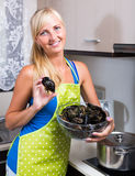 Blondie in apron with bowl of mussels Stock Photography