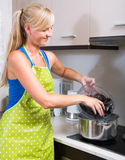 Blondie in apron with bowl of mussels Royalty Free Stock Photo