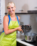 Blondie in apron with bowl of mussels Royalty Free Stock Photography