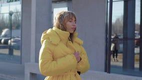 Blondie atractivo joven que camina en la ciudad que lleva la capa amarilla elegante en el otoño, pasando por un edificio metrajes