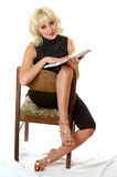 Blondie avläsning på en stol Arkivbilder