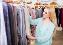 Blondie choosing  blouse in shop Royalty Free Stock Photos