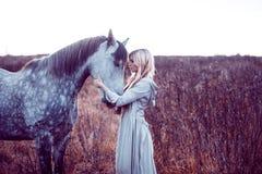 blondie de beauté avec le cheval dans le domaine, effet de la tonalité images stock