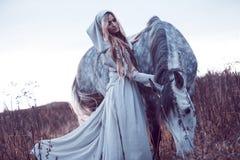 blondie de la belleza con el caballo en el campo, efecto del tono fotografía de archivo libre de regalías