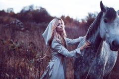 blondie de la belleza con el caballo en el campo, efecto del tono fotografía de archivo