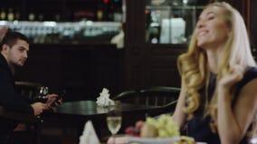 Blondie die aan de mens in restaurant van een andere plaats golven stock footage