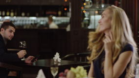 Blondie die aan de mens in restaurant van een andere plaats golven stock videobeelden