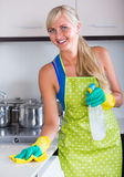 Blondie dusting in residential kitchen Royalty Free Stock Photography