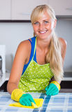 Blondie dusting in residential kitchen Stock Image