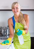 Blondie dusting in residential kitchen. Portrait of young blondie dusting in residential kitchen Royalty Free Stock Photography