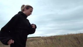 Blondie femminile che espone al sole in giacca a vento nera video d archivio