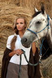 Blondie girl with horse. Beautiful young model standing near a horse stock photos
