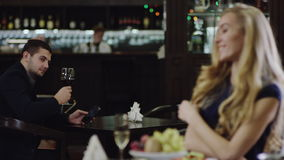 Blondie girl looking at man in restaurant from another place. Pair flirting in restaurant. woman looking at a man from another table stock footage