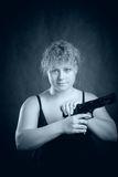 Blondie with gun. Pretty blondie with gun posing over dark background Stock Image