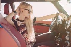 Blondie jong meisje bij het wiel van sportwagen Stock Afbeelding