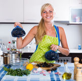 Blondie posing with fresh mussels in kitchen Royalty Free Stock Image