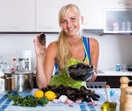 Blondie posing with fresh mussels in kitchen stock photo