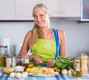 Blondie preparing veggies in kitchen Stock Image