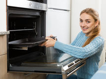 Blondie putting baking tray in kitchen oven. Portrait of happy blondie putting baking tray in kitchen oven Stock Photo