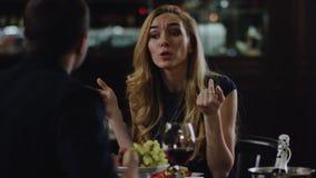 Blondie que discute con el socio en restaurante metrajes