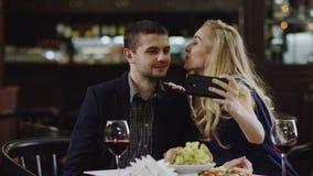 Blondie que toma el selfie con un hombre en café que lo besa metrajes