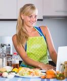 Blondie recherchant la recette dans l'Internet Images libres de droits