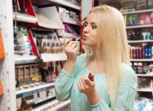 Blondie shopping in beauty store. Portrait of lovely young blondie shopping in beauty store Royalty Free Stock Photos